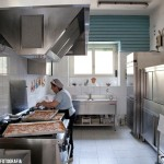 La cuoca prepara le pizze